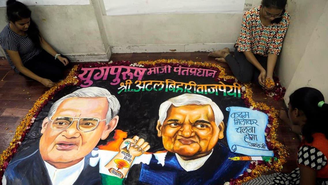 Students from an art school place flower petals around a painting of former Indian prime minister Atal Bihari Vajpayee in Mumbai, India, Thursday, Aug. 16, 2018. (AP)