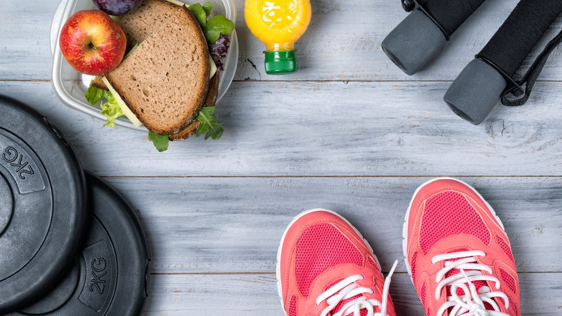 Fitness concept, pink sneakers, weight plates, dumbbells, sandwich - Stock image