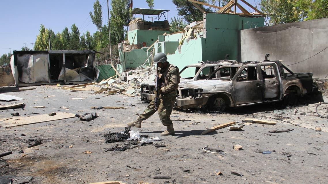 أحد أفراد قوات الأمن الأفغانية يقف بالقرب من مركبات الجيش المتضررة بعد هجوم لطالبان في مدينة غزنة