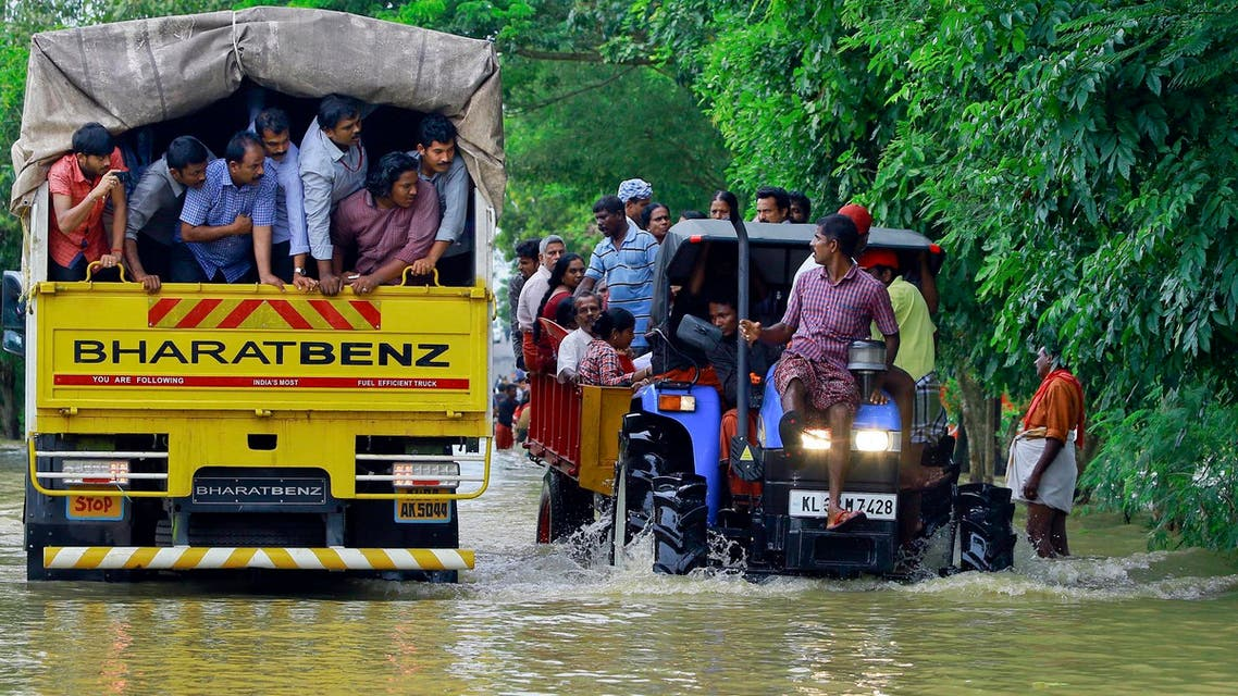 Flood affected people are rescued in a tractor, right as volunteers go for rescue work in a truck, left, at Kainakary in Alappuzha district, Kerala state, India, Friday, Aug. 17, 2018. (AP)