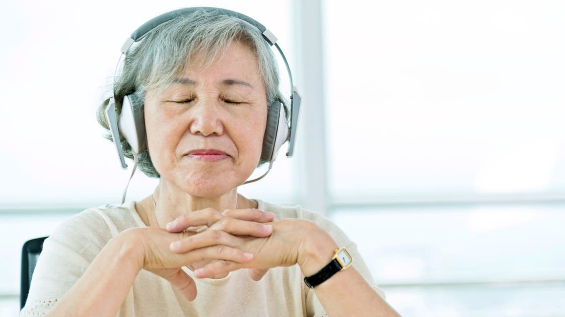 Senior asian woman listening to music with headphones