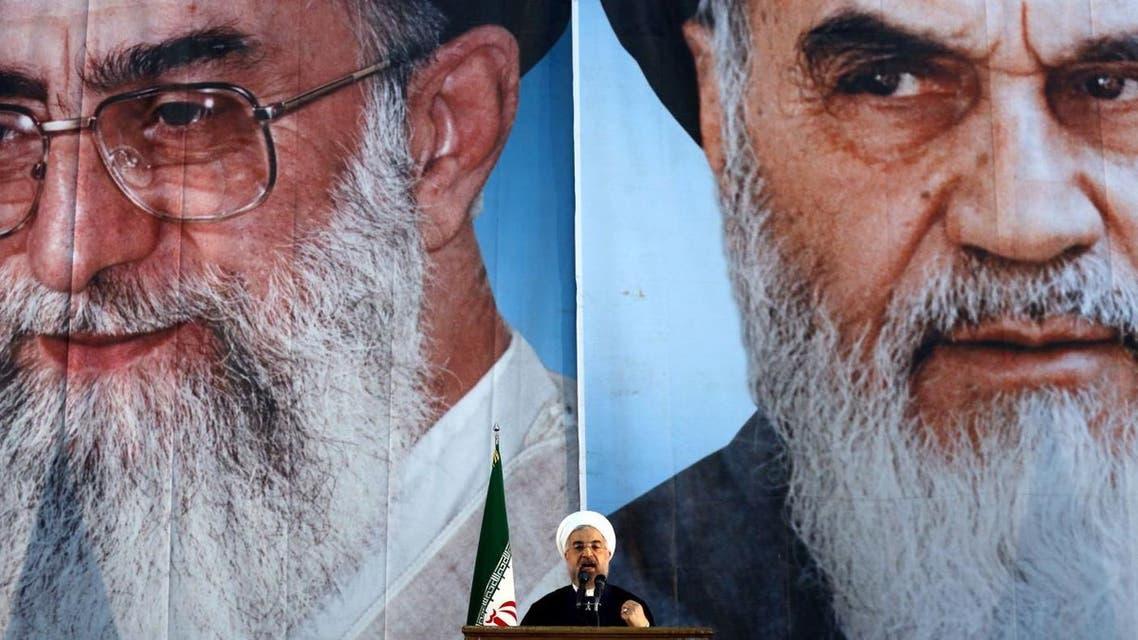 Iranian President Hassan Rouhani under portraits of Ayatollah Ali Khamenei and Ayatollah Ruhollah Khomeini in a suburb of Tehran. (AFP)