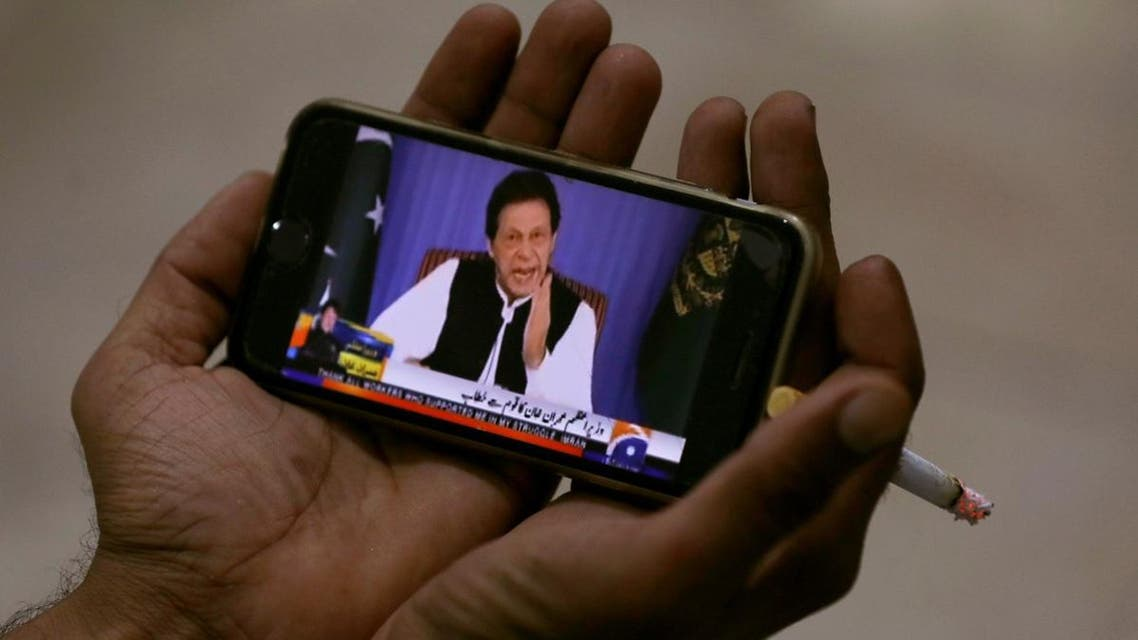 Journalist poses with a cell phone displaying Imran Khan speaking in his first televised address. (Reuters)