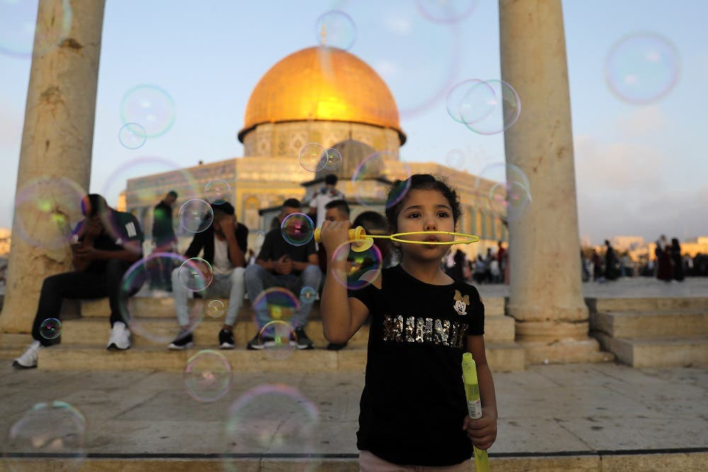 A young Palestinian girl blows soap bubbles near the Dome of the Rock at al-Aqsa Mosque compound in Jerusalem's old city on the first day of Eid al-Adha on August 21, 2018. (AFP)