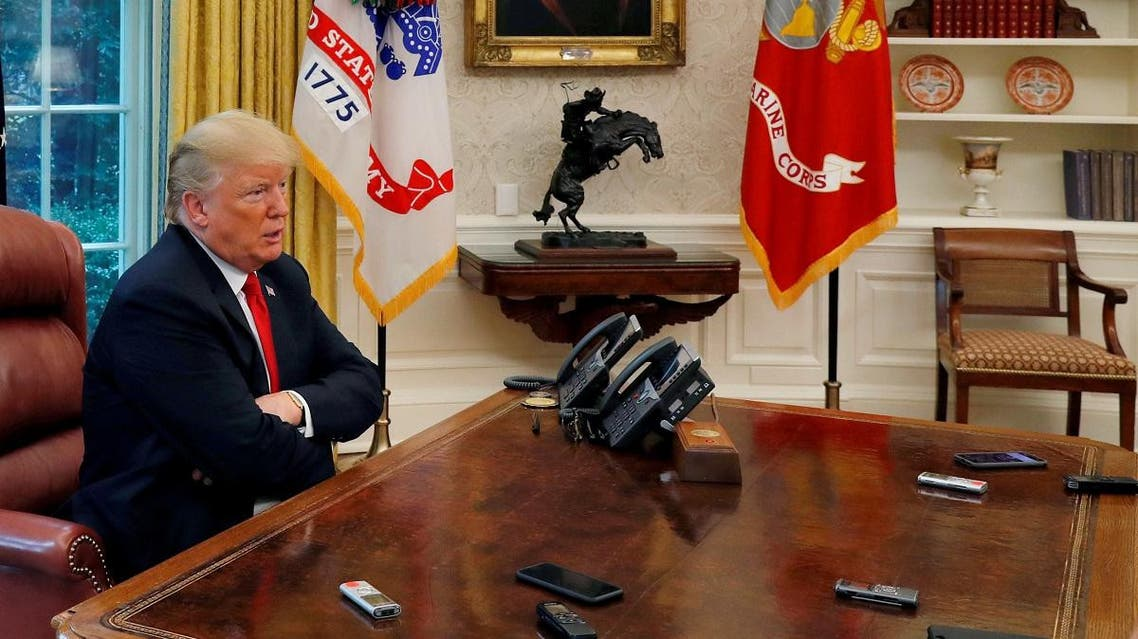 Trump answers question as eight devices record him during interview with Reuters in Oval Office of White House in Washington. (Reuters)
