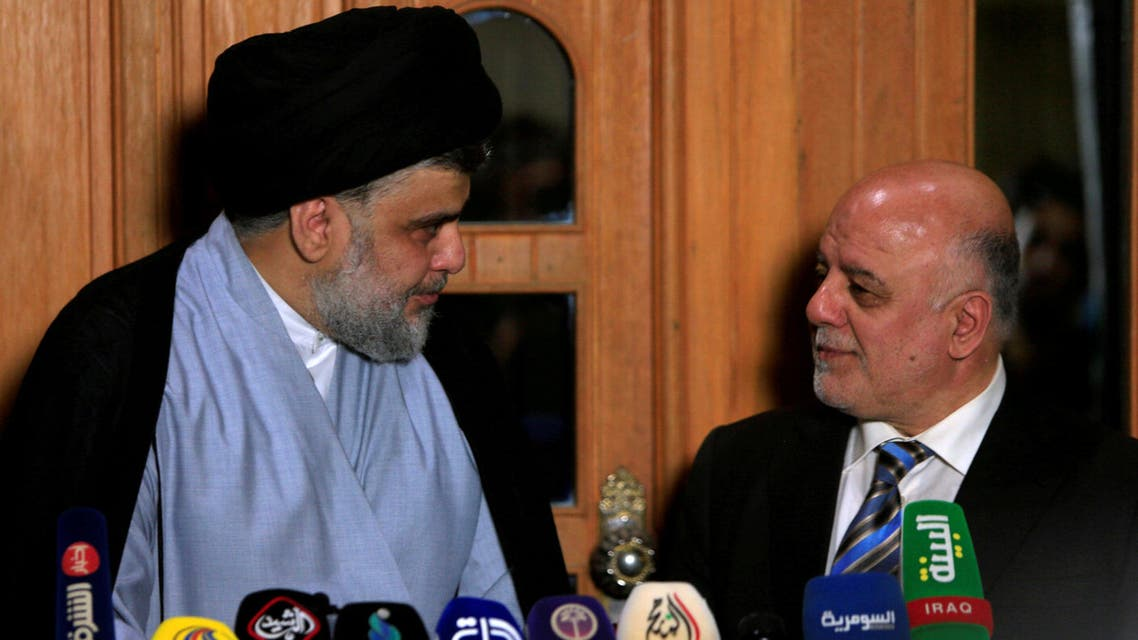 FILE PHOTO: Iraqi Shi'ite cleric Moqtada al-Sadr, who's bloc came first, looks at Iraqi Prime Minister Haider al-Abadi, who's political bloc came third in a May parliamentary election, during a news conference in Najaf, Iraq June 23, 2018. REUTERS/Alaa al-Marjani/ File Photo