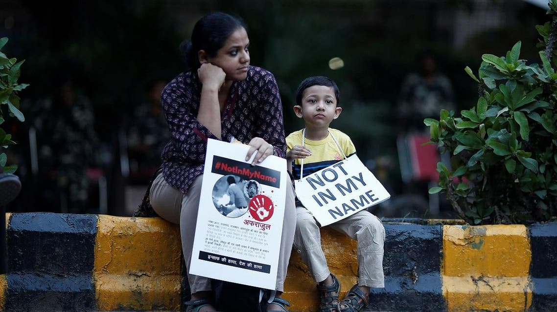 A woman and her son hold placards during a protest against, what the demonstrators say, recent mob lynchings across the country, in New Delhi. (Reuters)