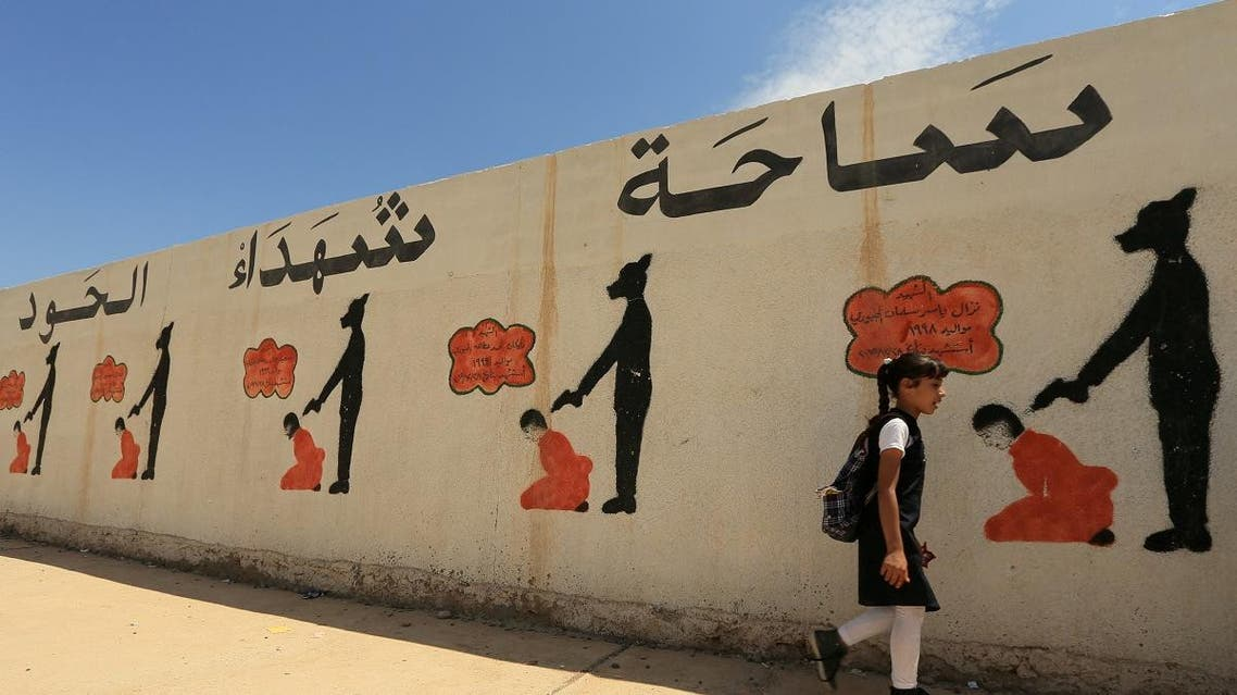 An Iraqi student walks past a school wall covered with drawings showing how ISIS militants executed their prisoners in Mosul. (Reuters)