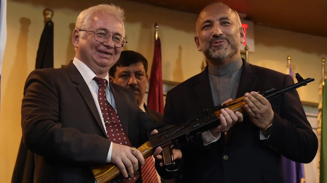 Russian Ambassador to Afghanistan Alexander Mantytskiy (L) hands over a AK-47 rifle to Afghan National Security Adviser Hanif Atmar (R) during a ceremony at a military airfield in Kabul.  (AFP)