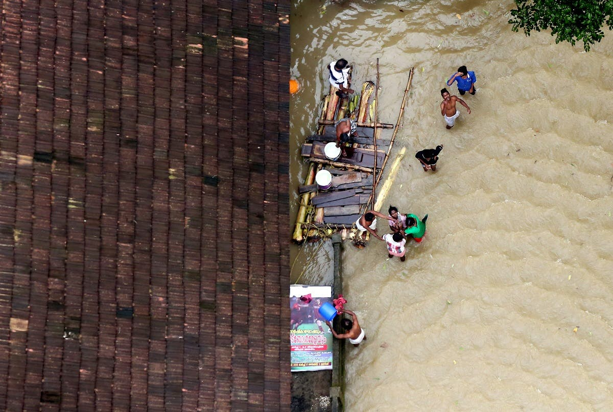 People wait for aid next to makeshift raft at a flooded area in the southern state of Kerala, India, August 19, 2018. (Reuters)