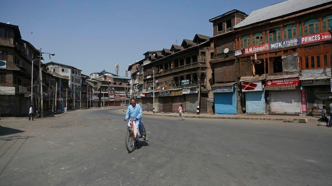 A Kashmiri man rides a bicycle past a closed market during a strike in Srinagar, Indian controlled Kashmir, Thursday, Aug. 30, 2018. (AP)