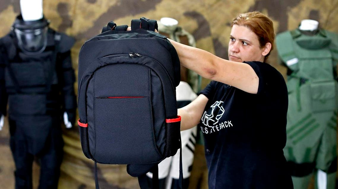 An employee of the Israeli protection gear manufacturer Masada Armour shows a new civilian bulletproof backpack (AFP)