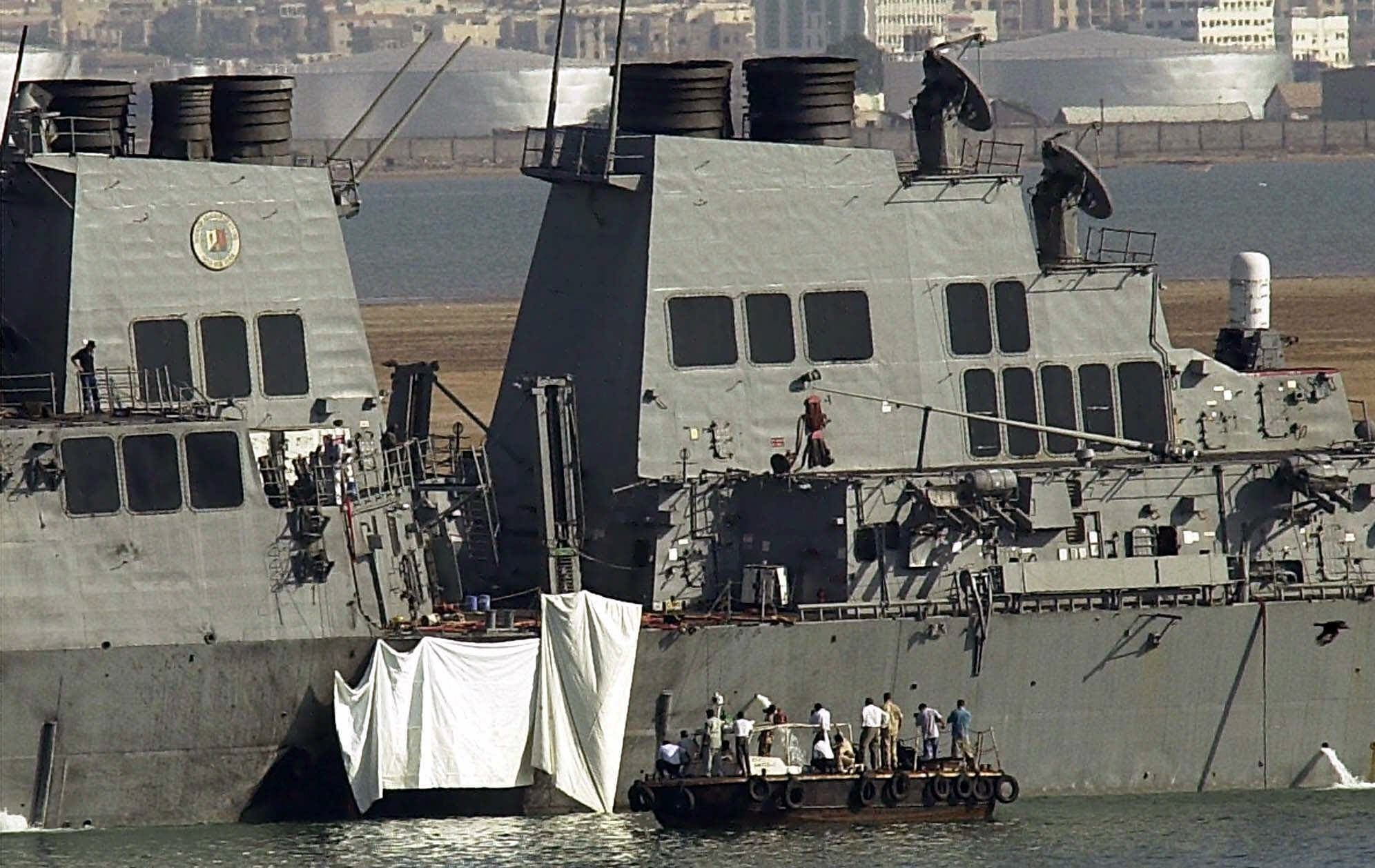Experts examine the hole on the side of the USS Cole in Aden on October 13, 2000. (AP)