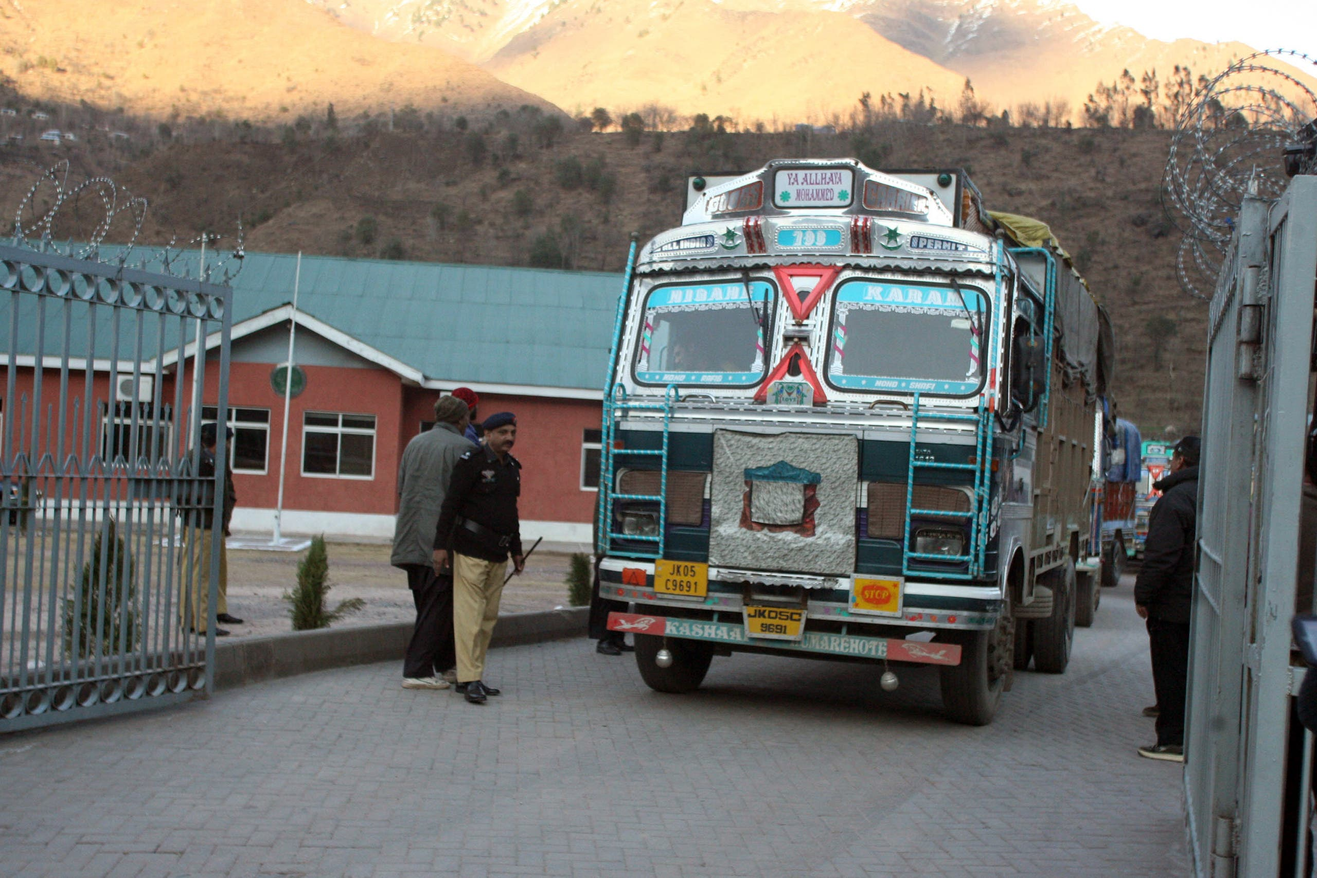 Pakistani policemen make way for Indian trucks as they leave the Trade Facilitation Centre before crossing the border in Chakoti on February 12, 2014. (AFP)