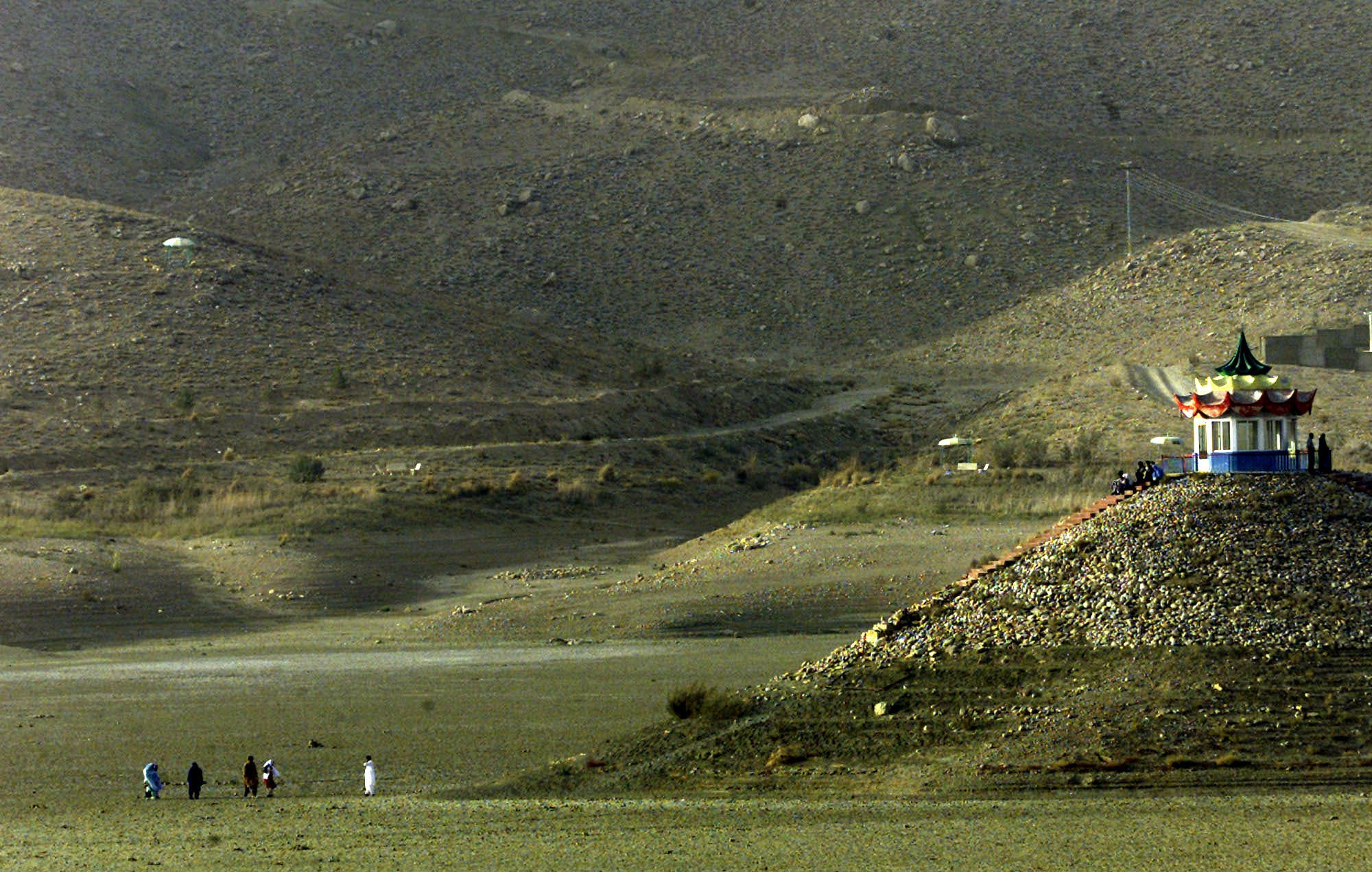 Pakistanis walk towards what was once an island, on the now dried-out Hanna Lake, outside the Baluchistan province capital of Quetta on Oct. 3, 2001. (AP)