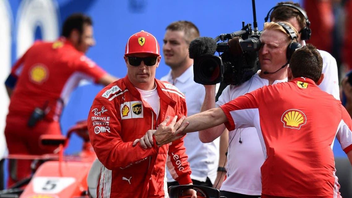 Ferrari's Finnish driver Kimi Raikkonen (L) celebrates winning the pole position with team members. (AFP)