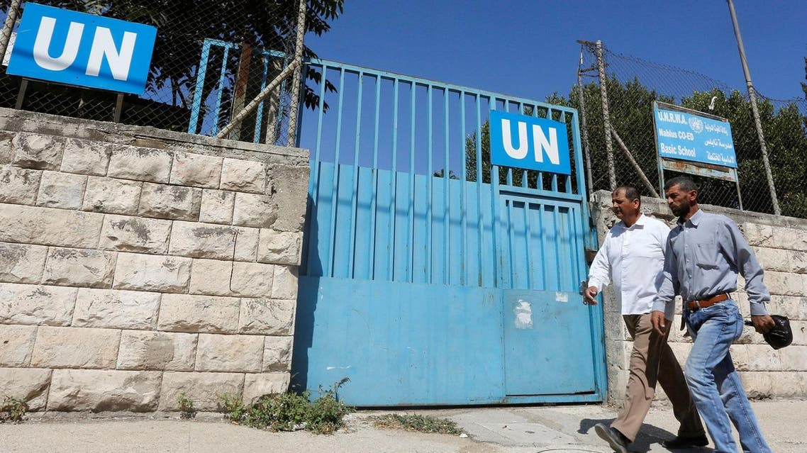 Two Palestinians walking past a school run by UNRWA in Nablus in the West Bank on August 13, 2018. Photo: Abed Omar Qusaini.