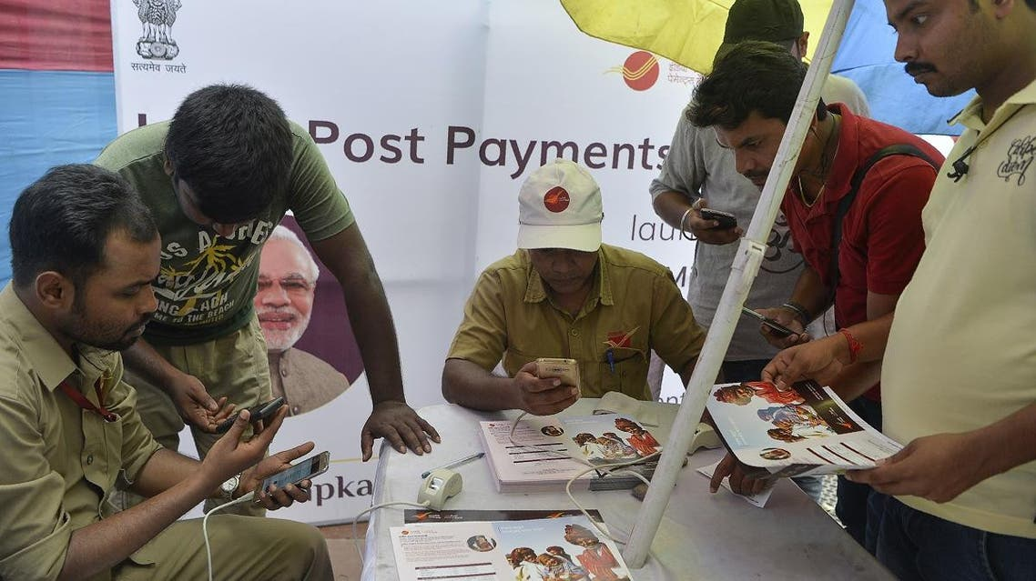 Indian post office employees help customers for opening new post office bank account 'India Post Payment Bank' in Siliguri on September 1, 2018. (AFP)