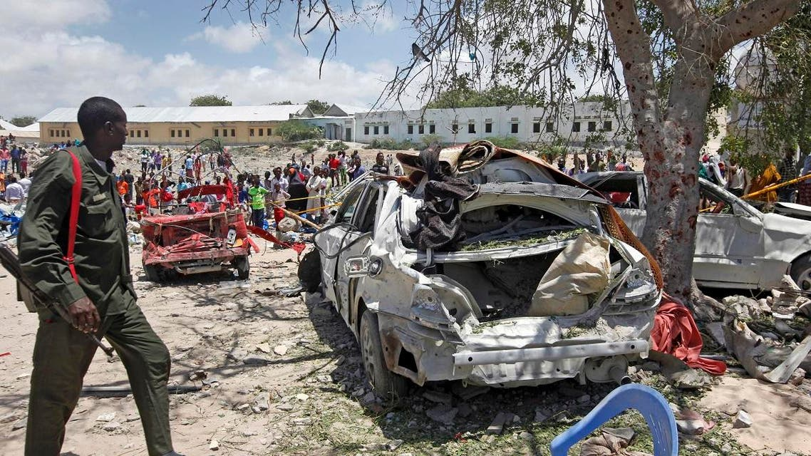 A Somali soldier walks near the wreckage of vehicles at the scene of a blast outside the compound of a district headquarters in the capital Mogadishu, Somalia Sunday, Sept. 2, 2018. (AP)