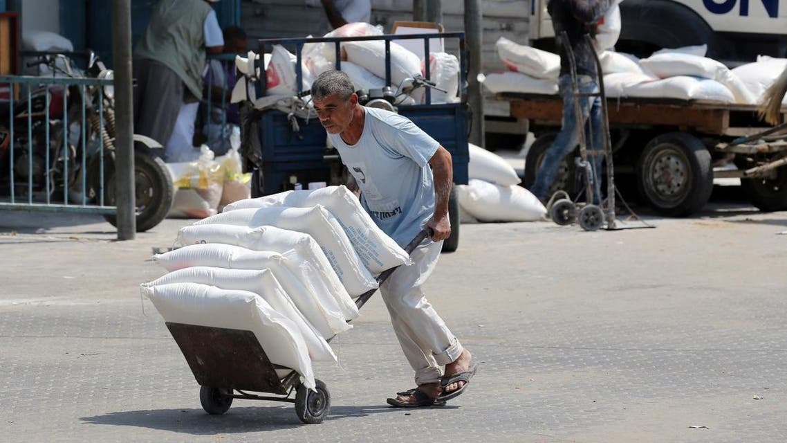 Palestinian man pushes a cart with bags of flour at an aid distribution center run by UNRWA in Khan Younis. (Reuters)