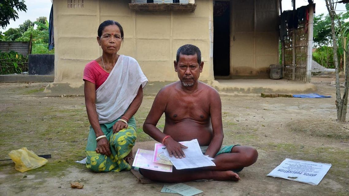 Nimai Hajong and his wife Sinibala Hajong sitting in front of their house in Bamunigaon village in Assam's Kamrup district. (AFP)