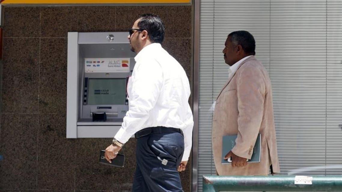 Men walk pass an automated teller machine (ATM) outside Bank Al Bilad in Riyadh, Saudi Arabia, April 25, 2016. (Reuters)