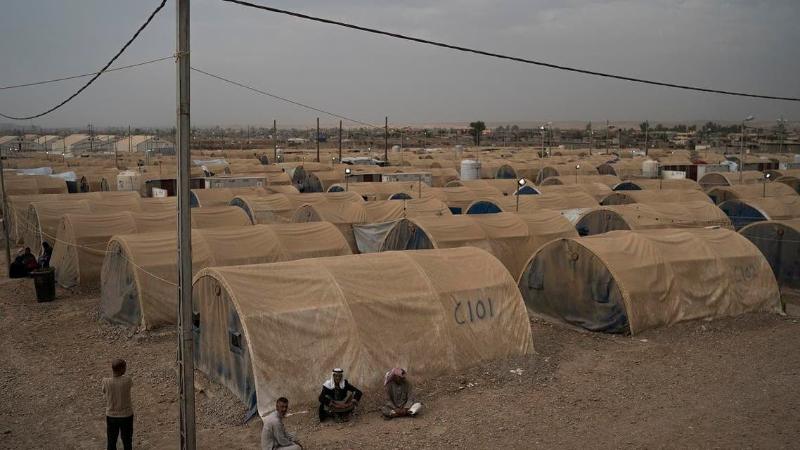 Displaced people sit outside their tents in the Hamam Alil camp, south of Mosul, Iraq, Tuesday, Nov. 7, 2017. (AP)