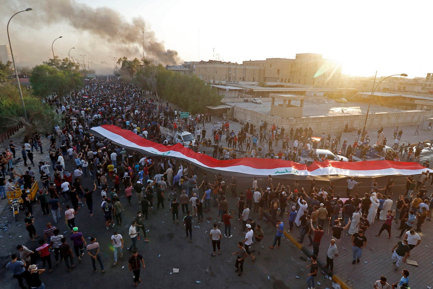 Iraqi protesters wave their national flag in front of official buildings as they demonstrate against the government and the lack of basic services in Basra on September 6, 2018. (AFP)