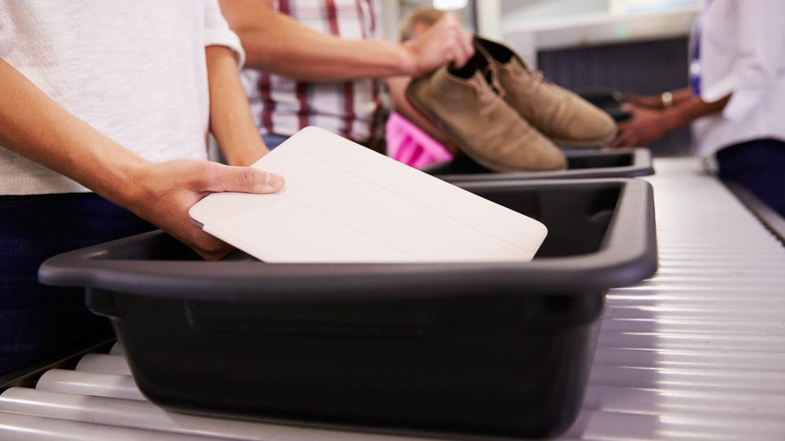 Man Puts Digital Tablet Into Tray For Airport Security Check - Stock image
