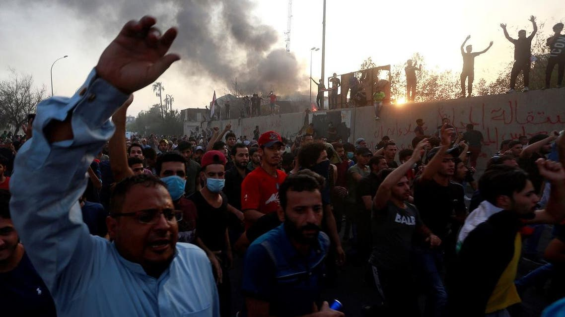 Iraqi protesters shout slogans during an anti-government protest near the burnt building of the government office in Basra. (Reuters)