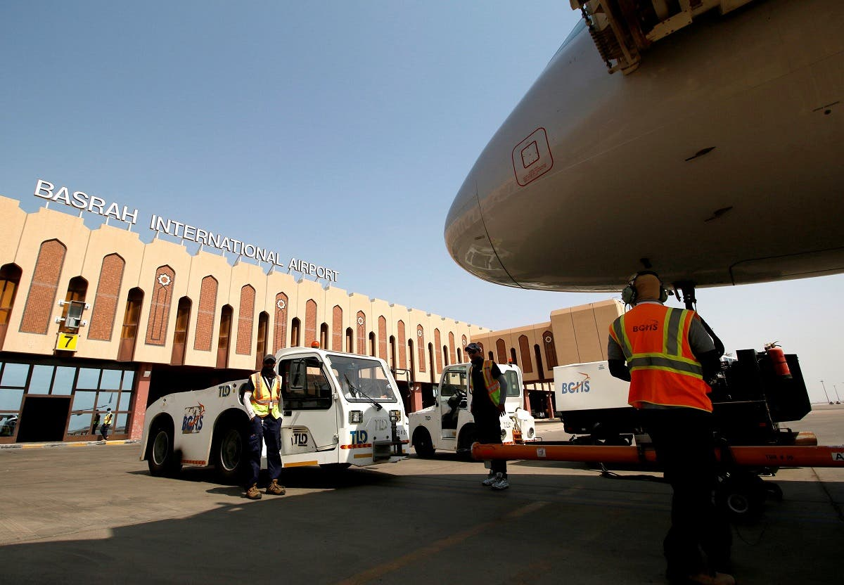 Airport workers are seen at Basra airport after it was targeted by rocket fire in Basra. (Reuters)