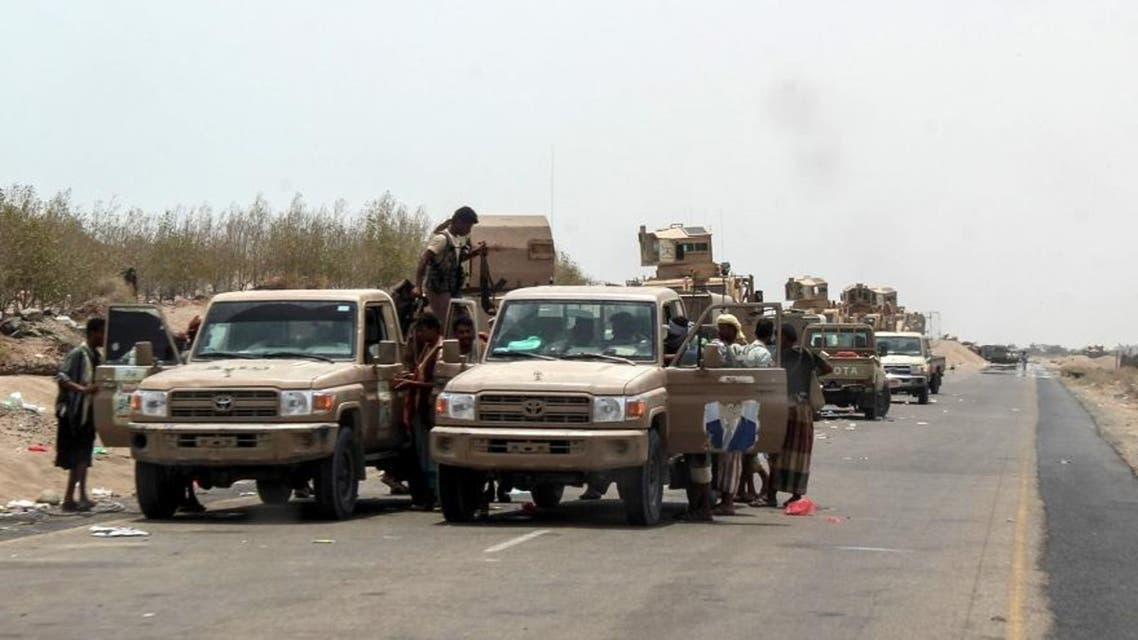 Yemeni fighters from the Amalqa (Giants) Brigades gather on the side of a road in Hodeidah. (AFP)
