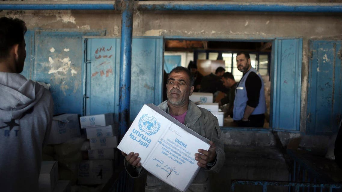 In this Jan. 14, 2018 photo, Palestinians receive food aid at a U.N. Relief and Works Agency warehouse in the Shati refugee camp, Gaza City. (AP)