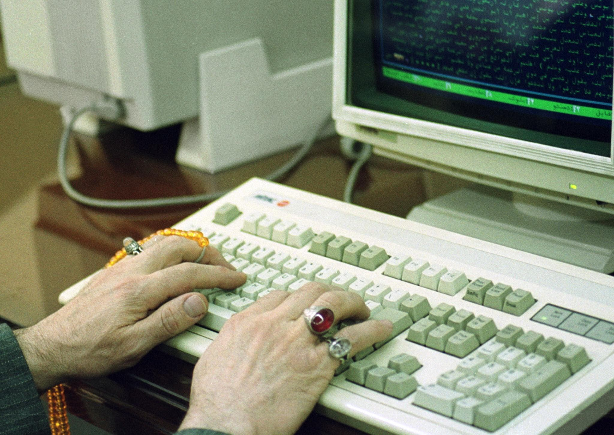 A religious scholar sporting rings and holding his worry beads types on a computer at a school in Qom on 18 February 2000. (AFP)