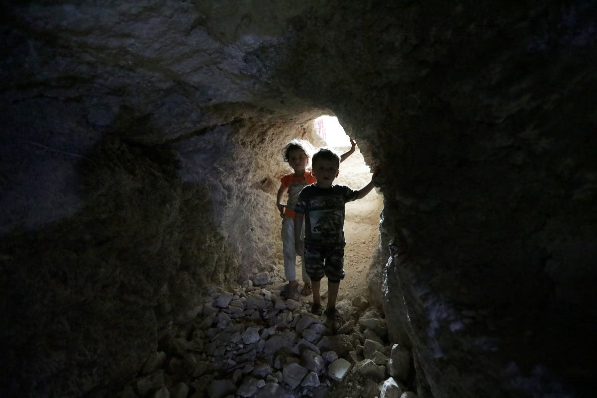 Children walk in a makeshift shelter in an underground cave in Idlib. (Reuters)