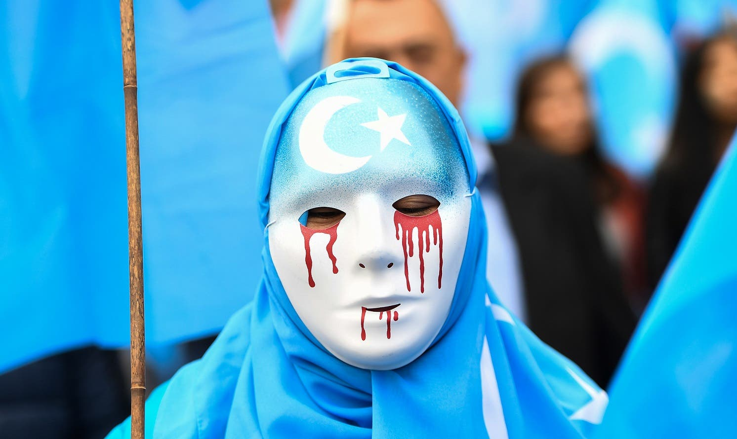 A person wearing a white mask with tears of blood takes part in a protest march in Brussels in support of ethnic Uighurs. (AFP)