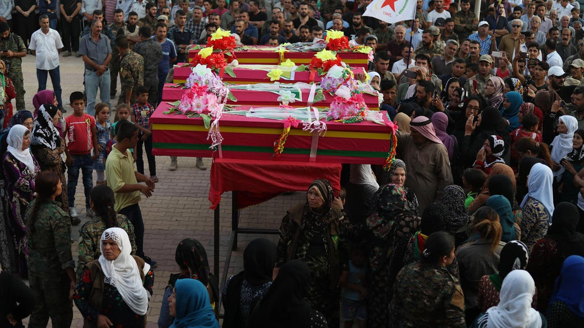 """Syrians mourn by the bodies of four fighters of the Syrian Democratic Forces (SDF), during their funeral in the northeastern city of Qamishli on September 14, 2018. Four SDF fighters were killed during battles in Deir Ezzor to oust Islamic State jihadists from the town of Hajin on the east bank of the Euphrates, the most significant remnant of the sprawling """"caliphate"""" the jihadists once controlled spanning Syria and Iraq."""