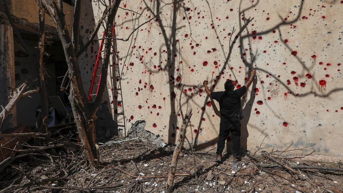 An Iranian Kurdish Peshmerga member of KDPI sprays red paint at holes in a wall made by shrapnel from a rocket attack in Arbil on September 12, 2018. (AFP)