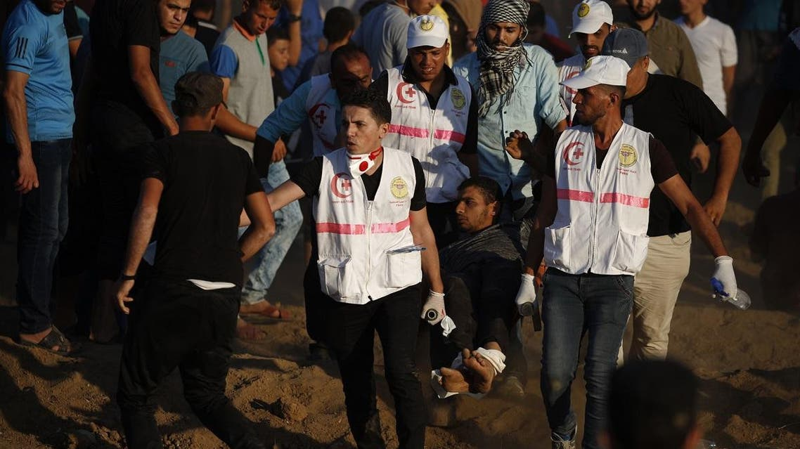 Paramedics carry a wounded Palestinian protester during a demonstration along the Israeli fence east of Gaza City on September 14, 2018. (AFP)