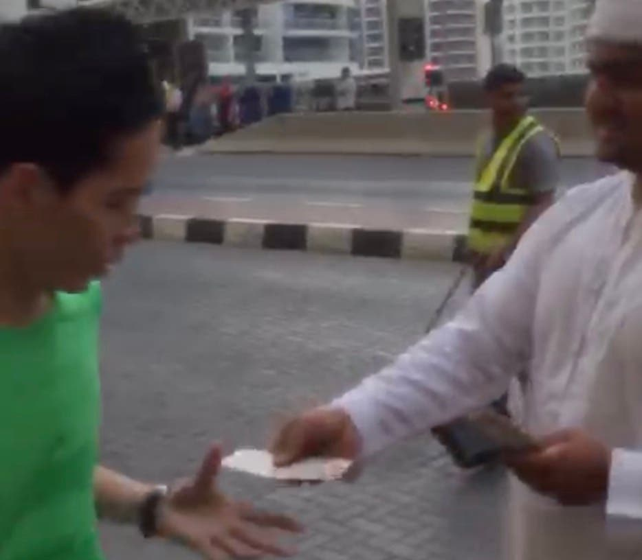 "Another video grab of a man in traditional Arab dress seen ""distributing cash among strangers"" in Dubai."