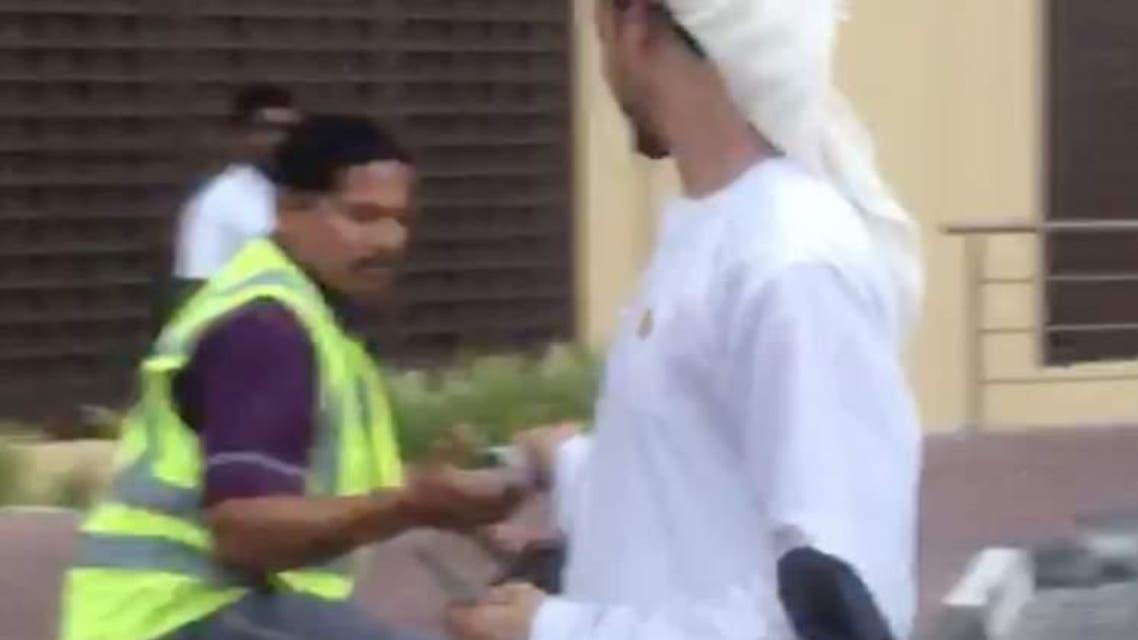 "Video grab of a man in traditional Arab dress seen ""distributing cash among strangers"" in Dubai."