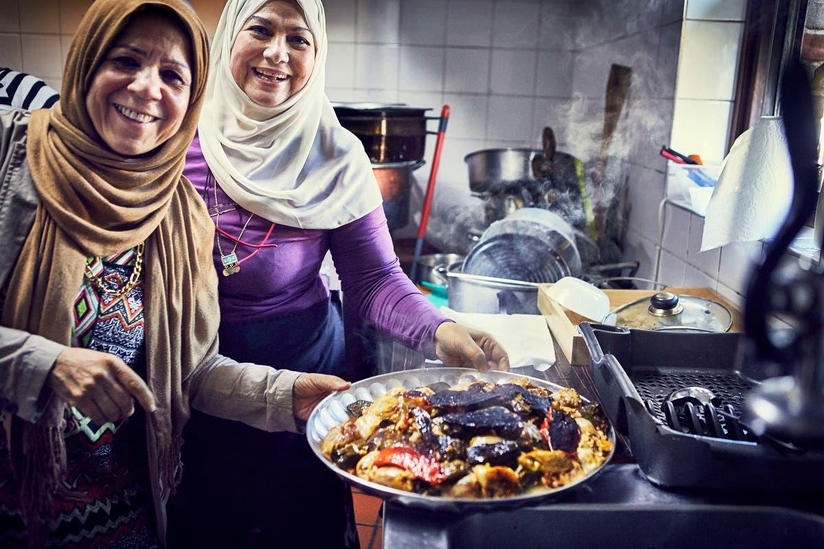 Intlak Al Saiegh and Ahlam Saeid cook in the Hubb Community Kitchen at the Al Manaar Muslim Cultural Heritage Centre. (Jenny Zarins/Handout via Reuters)