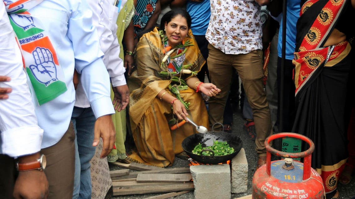 A Congress party supporter has vegetables hanging around her neck as she cooks some next to an empty cylinder of liquid petroleum gas during a protest in Bangalore on Sept. 10, 2018. (AP)