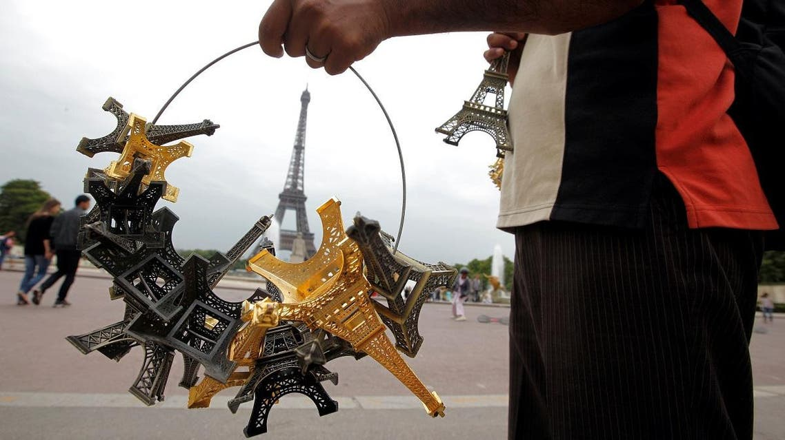 A souvenir vendor sells Eiffel tower models for tourists in front the Eiffel Tower at the Trocadero in Paris. (Reuters)