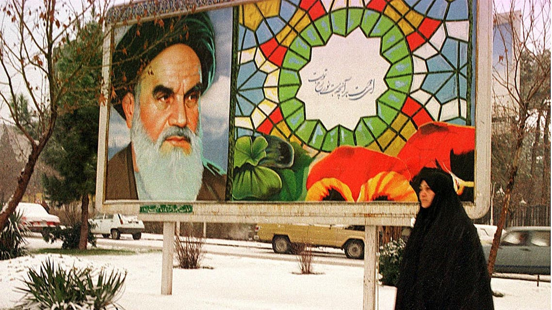 An Iranian woman passes by a billboard showing late Ayatollah Khomeini in Tehran. (File photo: AFP)