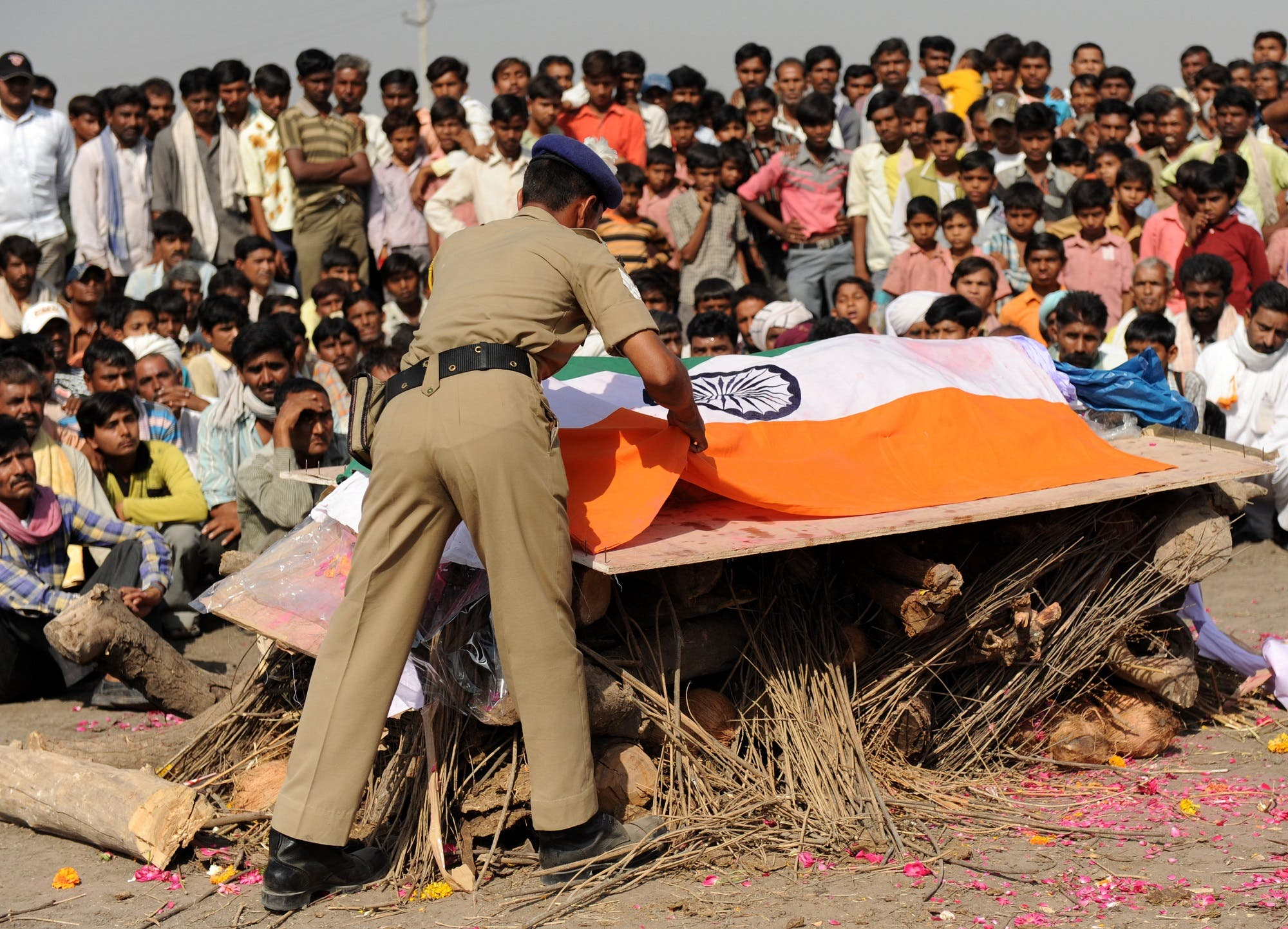A CRPF officer removes the national flag from the coffin of his colleague near Ahmedabad on March 20, 2010. (AFP)