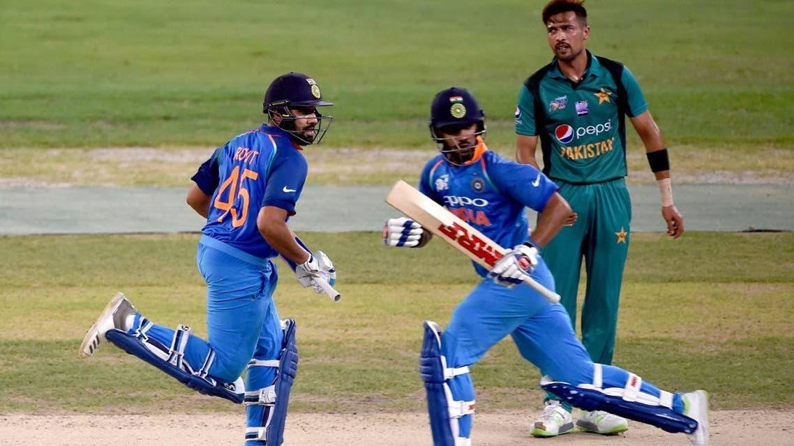 Indian captain Rohit Sharma (L) and Shikhar Dhawan (C) run between the wickets during the one day international (ODI) Asia Cup cricket match against Pakistan (AFP)