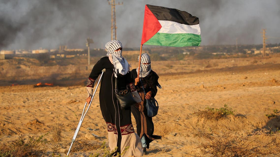 Palestinian demonstrators carry national flag during a protest in Beit Lahia on September 24, 2018. (AFP)