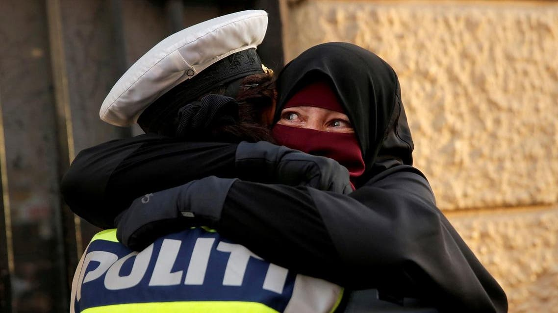 Ayah, a wearer of the niqab weeps as she is embraced by a police officer during a demonstration against the Danish face veil ban in Copenhagen. (Reuters)