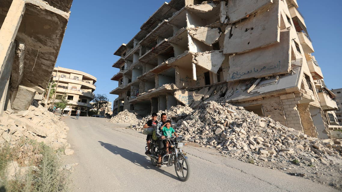Syrian men ride a motorcycle past heavily-damaged buildings in the rebel-held town of Maaret al-Numan, in the north of Idlib province on September 27, 2018.